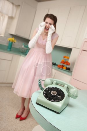 Photo for Young Caucasian woman weeps near a phone in a retro-style kitchen scene - Royalty Free Image