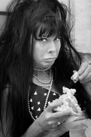 Photo for Unhappy black-haired woman with broken doll weeps - Royalty Free Image
