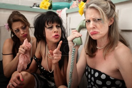 Photo for Upset woman with drunk friends on phone in kitchen - Royalty Free Image