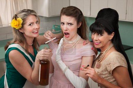 Photo pour Jeune femme avec ses amis fumant et buvant dans la cuisine - image libre de droit