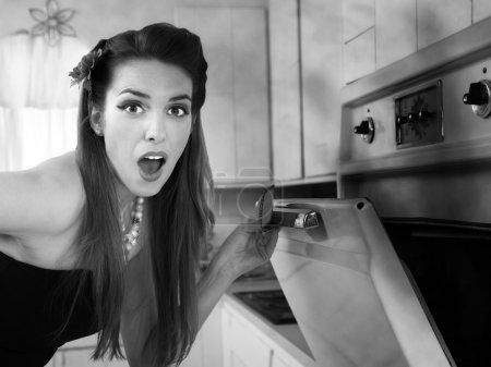 Photo pour Surpris belle ménagère caucasienne dans cuisine vérifie son four - image libre de droit