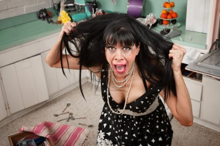 Photo for Desperate housewife pulling her hair in a messy kitchen - Royalty Free Image