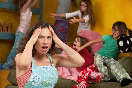 Photo for Upset mother with hands on head among mischievous little girls - Royalty Free Image