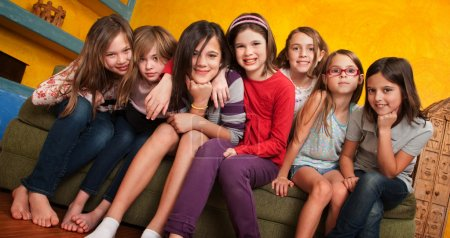 Photo for Group of seven little girls seated on a couch - Royalty Free Image