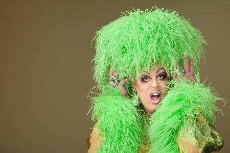 Photo pour Choqué drag queen, holding de chapeau boa sur fond vert - image libre de droit