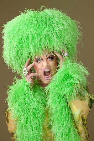 Photo pour Grande femme porter lourd maquillage et chapeau boa sur fond vert - image libre de droit