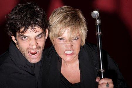 Evil Caucasian fortuneteller couple hold a scepter...