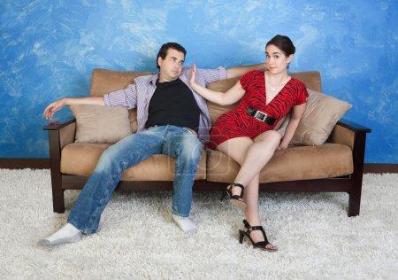 Photo pour Belle femme repousse homme bâclée sur canapé - image libre de droit