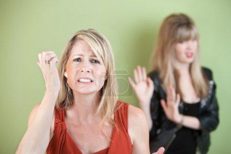 Photo pour Mère malheureuse avec une fille frustrée sur fond vert - image libre de droit
