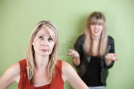 Photo pour Maman déçue avec une fille frustrée en arrière-plan - image libre de droit