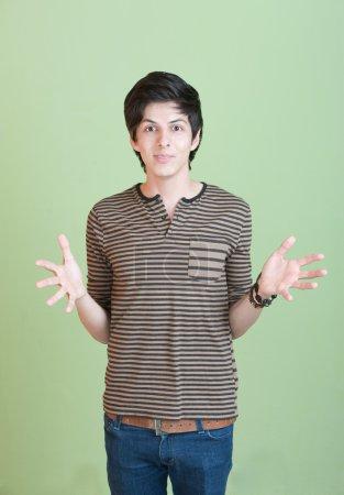 Photo pour Adolescent hispanique avec les mains ouvertes sur fond vert - image libre de droit