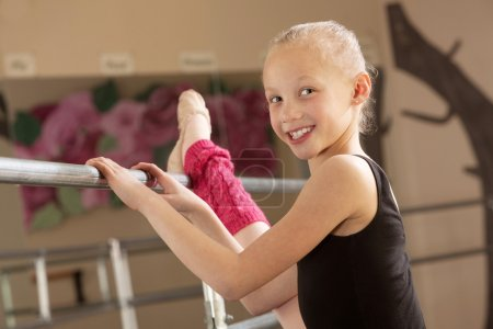 Photo for Little ballerina girl with leg on bar in dance studio - Royalty Free Image