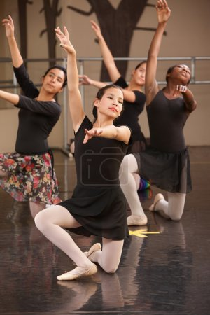 Photo for Four young ballet performers kneeling on floor - Royalty Free Image
