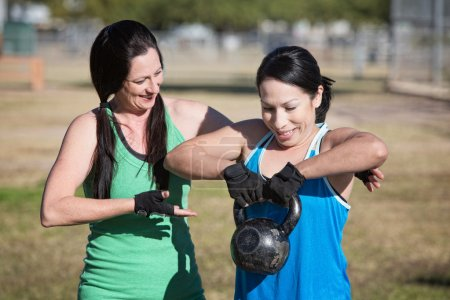 Woman Assisting Student with Weights