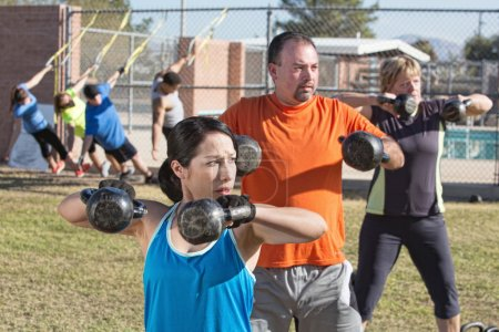 Men and women in boot camp fitness class outdoors...