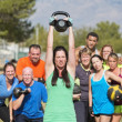 Young woman struggling with weighs in fitness clas...