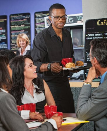 Photo for Smiling handsome server bringing scones to business people - Royalty Free Image
