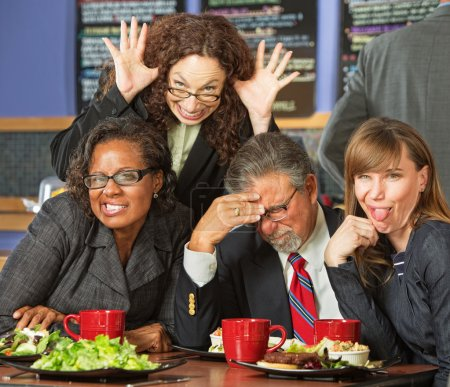 Photo for Embarrassed man with coworkers making faces in cafe - Royalty Free Image
