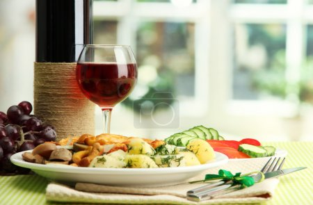 Photo for Roast chicken cutlet with boiled potatoes and cucumbers, glass of wine on green table cloth in cafe interior - Royalty Free Image