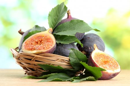Ripe sweet figs with leaves in basket, on wooden table, on green background
