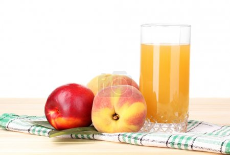 Ripe peaches and juice on wooden table on white background
