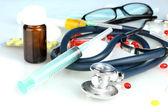 Léky a stetoskop na modrém pozadí detail