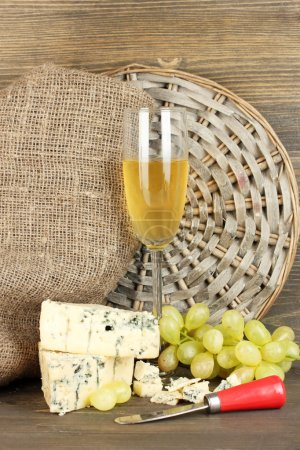 composition of blue cheese and a glass of wine with grapes on wooden backgr