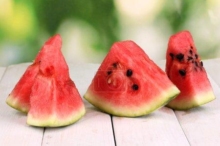 Photo pour Tranches de melon d'eau douce sur une table en bois sur fond naturel - image libre de droit