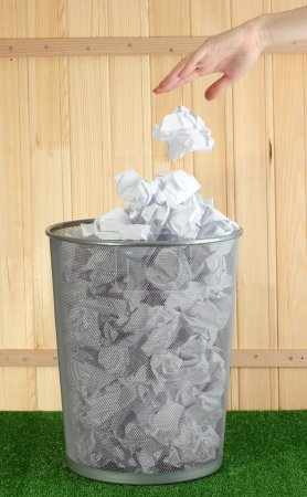 Photo pour Main allant des ordures dans une poubelle métallique de papier sur herbe sur fond en bois - image libre de droit