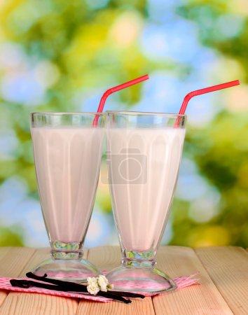 Vanilla milk shakes on wooden table on bright background