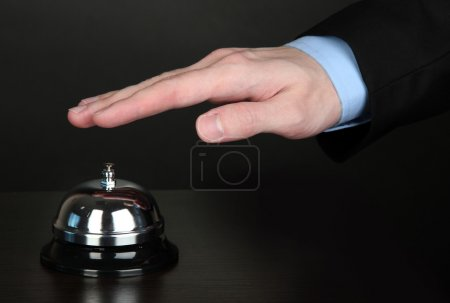 Photo for Hand ringing in service bell on wooden table on black background - Royalty Free Image