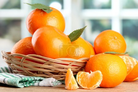 Photo for Tangerines with leaves in a beautiful basket, on wooden table on window background - Royalty Free Image
