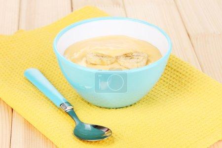 Yogurt with banana on wooden table