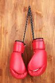 Rote Boxhandschuhe hängen hölzerne Hintergrund