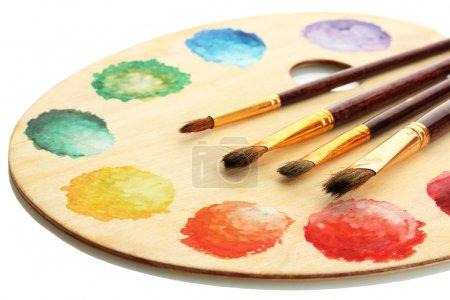 Photo pour Palette d'art en bois avec peinture et pinceaux isolés sur blanc - image libre de droit