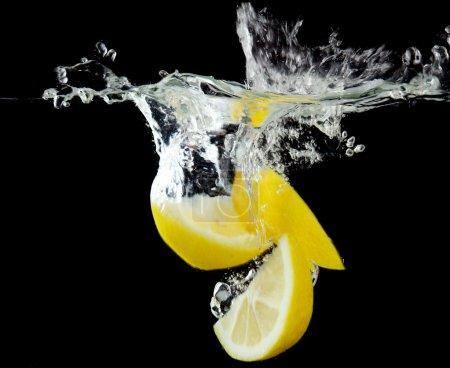 Photo pour Citron tranché dans l'eau sur fond noir - image libre de droit