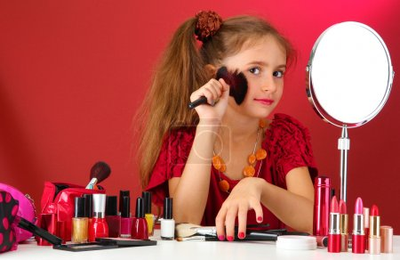 little girl in her mother's dress with make up brushes