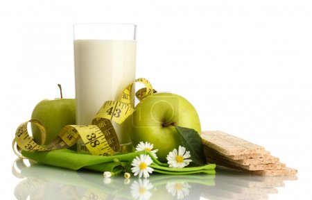 Glass of kefir, green apples, crispbreads and measuring tape isolated on wh