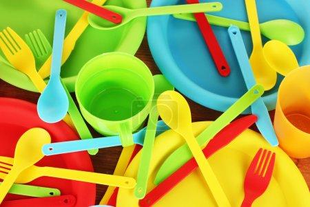Photo pour Lumineux vaisselle jetable en plastique, le gros plan de fond en bois - image libre de droit