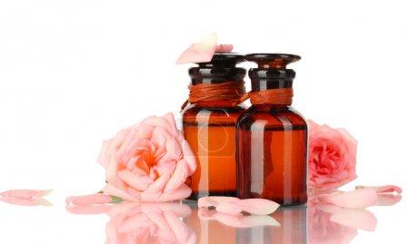 Photo pour Bouteilles d'huile et roses isolées sur blanc - image libre de droit