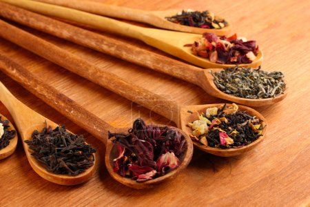 Assortment of dry tea in spoons, on wooden backgro...