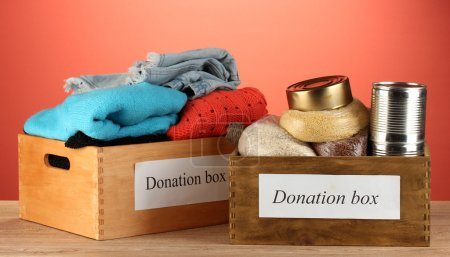 Donation boxes with clothing and food on red background close-up