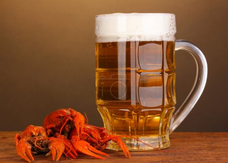 Photo for Tasty boiled crayfishes and beer on table on brown background - Royalty Free Image