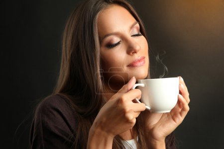 Beautiful young woman with cup of coffee on brown background