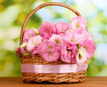 bouquet of eustoma flowers in basket, on wooden table, on green background
