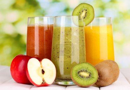Photo pour Jus de fruits frais sur une table en bois, sur fond vert - image libre de droit