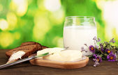 Butter on wooden holder surrounded by bread and milk on wooden table on natural background close-up