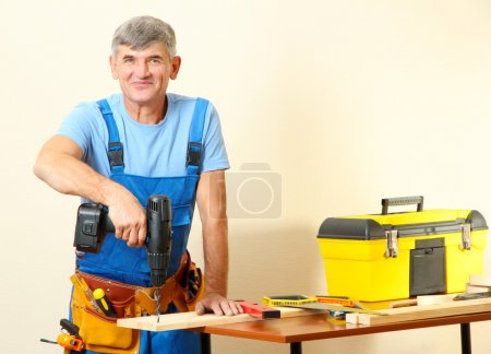 Builder drills board on table on wall background