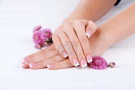 Photo pour Mains de femme avec français manucure et fleurs sur fond en bois blanc - image libre de droit