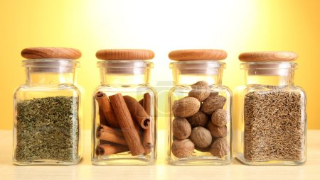 powder spices in glass jars on yellow background